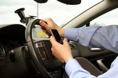 Biznesmen używa telefon komórkowego podczas gdy jadący samochód Zdjęcia Stock