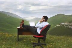 Biznesmen Używa telefon komórkowego Przy biurkiem W polu obraz stock