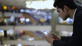 Biznesmen używa telefon komórkowego w zakupy centrum handlowym