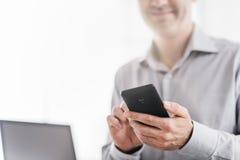 Biznesmen używa smartphone w jego biurze Obraz Stock
