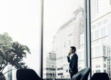 Biznesmen używa telefon komórkowego blisko biurowego okno przy korytarzem ar Obraz Stock