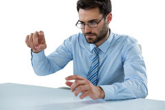 Biznesmen udaje dotykać niewidzialnego przedmiot przy biurkiem Zdjęcia Stock