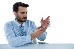Biznesmen udaje dotykać niewidzialnego przedmiot przy biurkiem Zdjęcie Stock