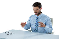 Biznesmen udaje dotykać niewidzialnego przedmiot przy biurkiem Fotografia Stock