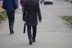 Biznesmen Ufny młody człowiek w jego rękawie i patrzeć oddalony podczas gdy stojący outdoors z pejzażem miejskim w zdjęcie royalty free