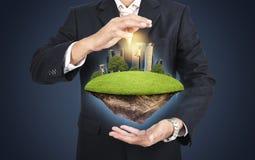 Biznesmen utrzymuje zieloną wyspę z skycraper miastem wewnątrz w kostiumu Zdjęcie Royalty Free