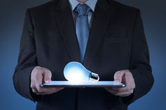 Biznesmen używa pastylki komputerową narastającą żarówkę Obraz Royalty Free