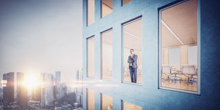 Biznesmen wśrodku drapacza chmur, lookng przy miastem zdjęcie royalty free