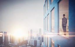 Biznesmen wśrodku drapacza chmur, lookng przy miastem zdjęcia stock