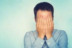 Biznesmen w błękitnym koszulowym nakryciu jego twarz z rękami nad błękitnym tłem mężczyzna chuje jego łzy zdjęcie royalty free