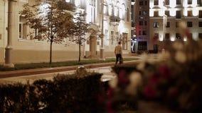 Biznesmen w beżowej kurtce z torbą w jego ręce chodzi przez nocy miasta zdjęcie wideo