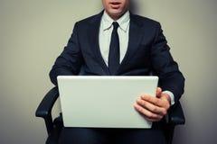 Biznesmen w biurowym krześle pracuje na laptopie fotografia stock
