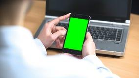 Biznesmen w biurowym scrolling wiszącej ozdoby zieleni ekranu telefonie komórkowym wpisywał gest zdjęcie wideo