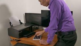 Biznesmen w biurze drukuje dokumenty na drukarce zbiory wideo