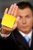 Biznesmen w biurze z pustą adhezyjną notatką wtykającą jego ręka Zdjęcie Royalty Free
