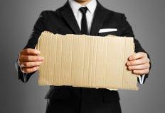 Biznesmen w czarnym kostiumu, białej koszula i krawacie, trzyma kawałek Obraz Stock