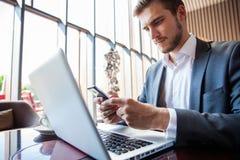 Biznesmen w czarnym kostiumu, działanie na laptopie używać mobilnego mądrze telefon, wyszukujący internet i pisać dalej, obrazy royalty free