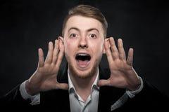 Biznesmen w czarnym kostiumu krzyczy podnoszący jego ręki up Zdjęcie Royalty Free