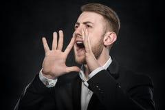 Biznesmen w czarnym kostiumu krzyczy podnoszący jego ręki up Obrazy Stock