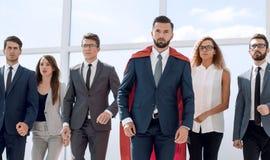Biznesmen w czerwonej bohater pelerynie i jego biznesowej drużynie obraz stock