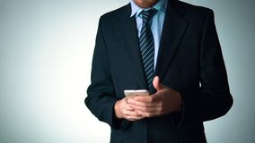 Biznesmen w eleganckim kostiumu używa telefon towarzyskość, elegancja zbiory