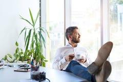 Biznesmen w jego biurze, mieć przerwę, pije kawę Zdjęcie Royalty Free