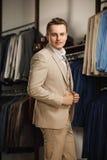 Biznesmen w klasycznej kamizelce przeciw rzędowi kostiumy w sklepie Młody elegancki mężczyzna w czarnej sukiennej kurtce Ja jest  Zdjęcie Stock