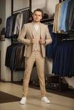 Biznesmen w klasycznej kamizelce przeciw rzędowi kostiumy w sklepie Młody elegancki mężczyzna w czarnej sukiennej kurtce Ja jest  Zdjęcia Stock