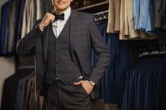 Biznesmen w klasycznej kamizelce przeciw rzędowi kostiumy w sklepie Młody elegancki mężczyzna w czarnej sukiennej kurtce Ja jest  Obraz Stock