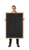 Biznesmen w kostium pozyci i mienia blackboard w drewnianej ramie, odosobnionej na białym tle obrazy stock