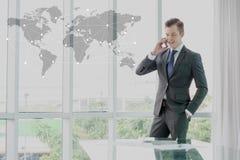 Biznesmen w kostiumu mówieniu na telefonie komórkowym, biznesowy globaliza Obrazy Royalty Free