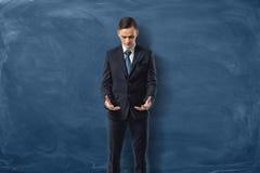 Biznesmen w kostiumu patrzeć jego puste ręki na zmroku i pozyci - błękitny tło fotografia royalty free
