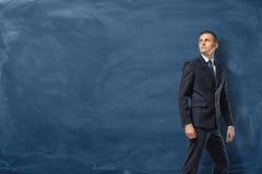 Biznesmen w kostiumu stoi naprzód i pewnie patrzeje na błękitnym blackboard tle obrazy royalty free