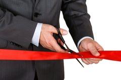 Biznesmen w kostiumu tnącym czerwonym faborku z parą nożyce fotografia royalty free