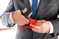 Biznesmen w kostiumu tnącym czerwonym faborku z parą nożyce iso Zdjęcia Royalty Free