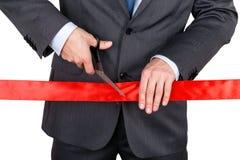 Biznesmen w kostiumu tnącym czerwonym faborku z parą nożyce iso Zdjęcia Stock