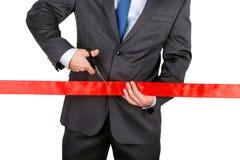Biznesmen w kostiumu tnącym czerwonym faborku z parą nożyce iso Obraz Stock