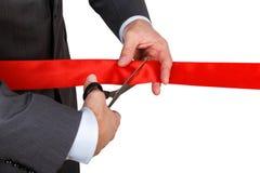 Biznesmen w kostiumu tnącym czerwonym faborku z parą nożyce iso Obrazy Royalty Free