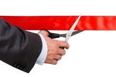 Biznesmen w kostiumu tnącym czerwonym faborku z parą nożyce iso Obraz Royalty Free