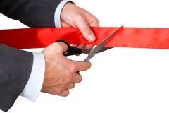 Biznesmen w kostiumu tnącym czerwonym faborku z parą nożyce iso Zdjęcie Stock
