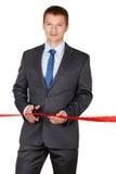Biznesmen w kostiumu tnącym czerwonym faborku z parą nożyce iso Fotografia Stock