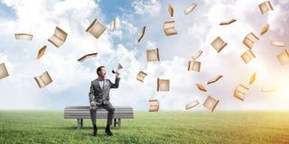Biznesmen w lecie parkowym i książki ogłaszający coś w głośniku latamy wokoło zdjęcie royalty free