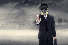 Biznesmen w masce gazowej ostrzega zatrzymywać zanieczyszczenie fotografia stock
