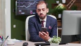 Biznesmen w nowożytnym biurze z kreatywnie projektem ma wideo wezwanie przez jego telefonu zbiory wideo