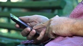 Biznesmen w Parkowym obsiadaniu na ławka tekscie Używać telefon komórkowy sieć bezprzewodową fotografia royalty free