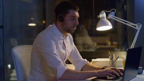 Biznesmen w słuchawki z laptopem przy nocy biurem zbiory