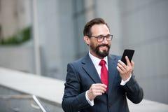 Biznesmen w szkłach używać mądrze telefon na biurowym przejściu z miasto budynku tłem Pojęcie ludzie biznesu zdjęcie stock