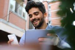 Biznesmen w ulicznej cukiernianej używa technologii z bliska obraz stock