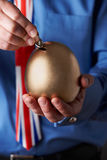 Biznesmen W Union Jack krawata kładzenia monecie Z jajkiem Kształtny Savin Zdjęcie Royalty Free
