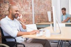 Biznesmen w wózku inwalidzkim pracuje przy jego biurkiem na telefonie Fotografia Stock